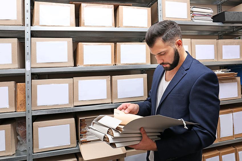 Mann med dokumenter i arkiv