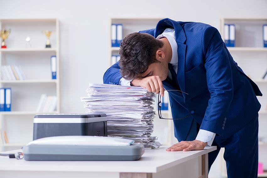 Mann som lener hodet på en bunke med papirer foran en skanner