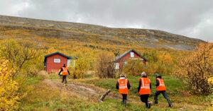 Personer på besiktigelse i Porsanger foran en hytte