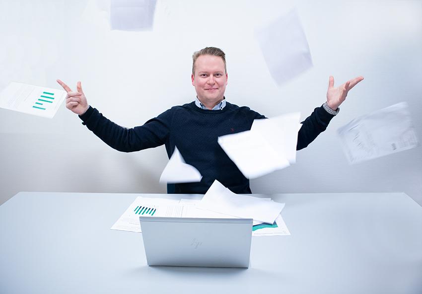 Mann foran PC som kaster papirark i luften