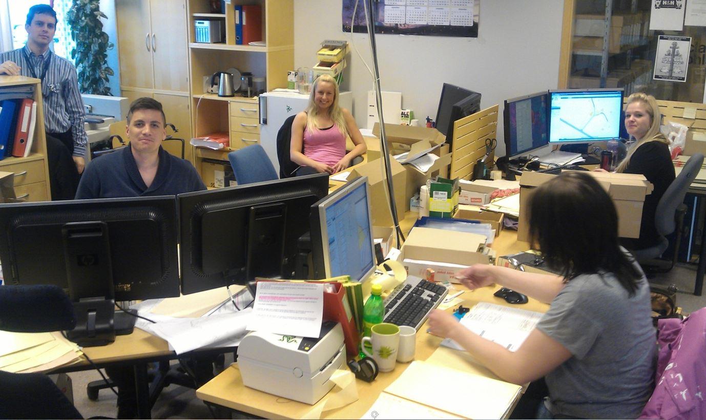 Skanningsmedarbeidere som sitter på sine arbeidsstasjoner