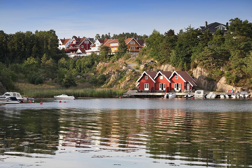 Bilde av en liten rød bryggerekke i Kristiansand kommune.